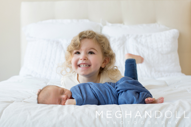 big-sister-smiles-with-new-brother-on-bed
