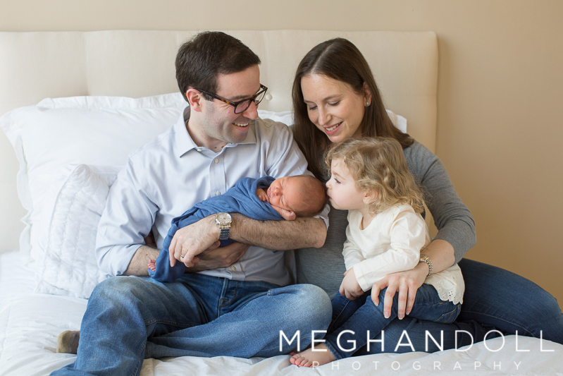family-snuggles-newborn-baby-boy-in-blue