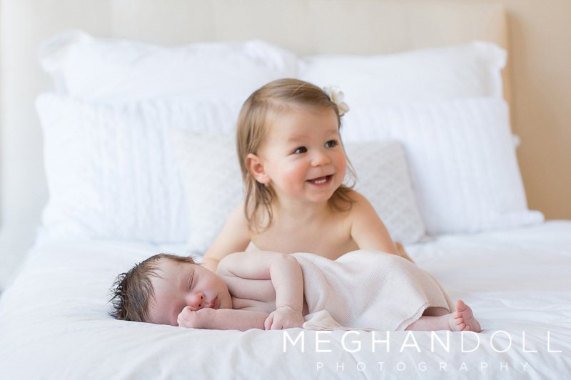 new-big-sister-smiles-on-bed-with-new-baby-sister