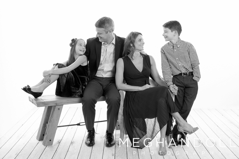 family-of-four-in-nice-clothes-smile-at-each-other