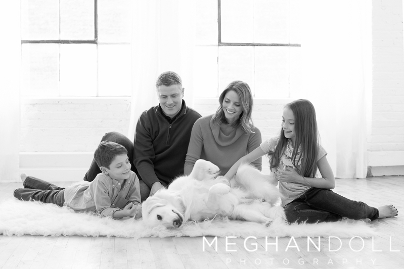 family-of-four-play-with-their-fuzzy-dog