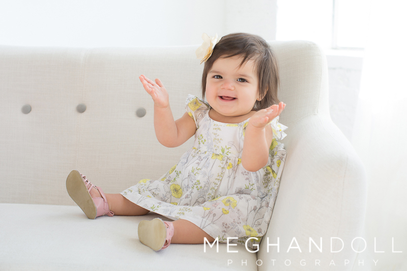 one-year-old-girl-claps-on-white-couch