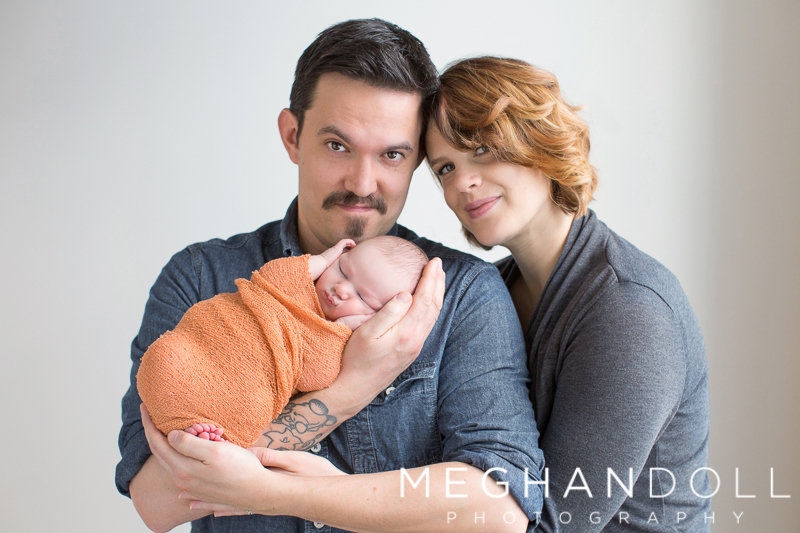 mom-and-dad-hold-newborn-son-in-orange