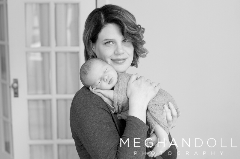 mom-holds-newborn-son-in-front-of-french-doors