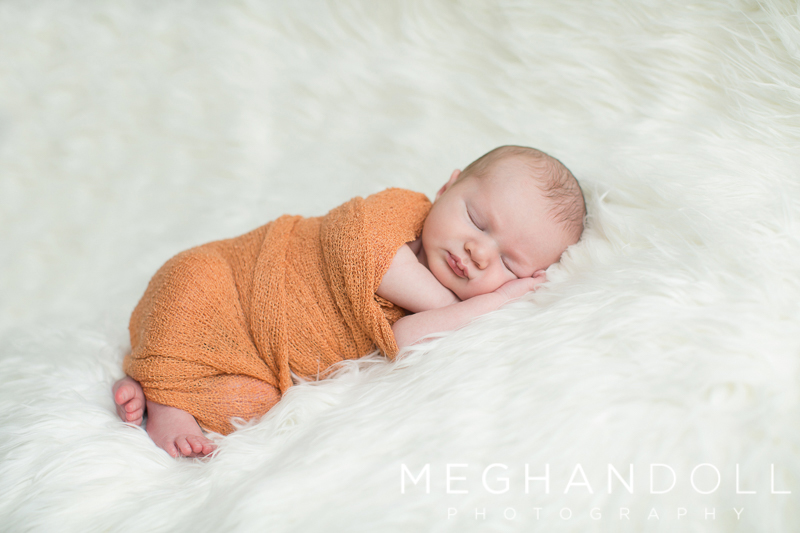 newborn-boy-in-orange-sleeps-on-furry-rug