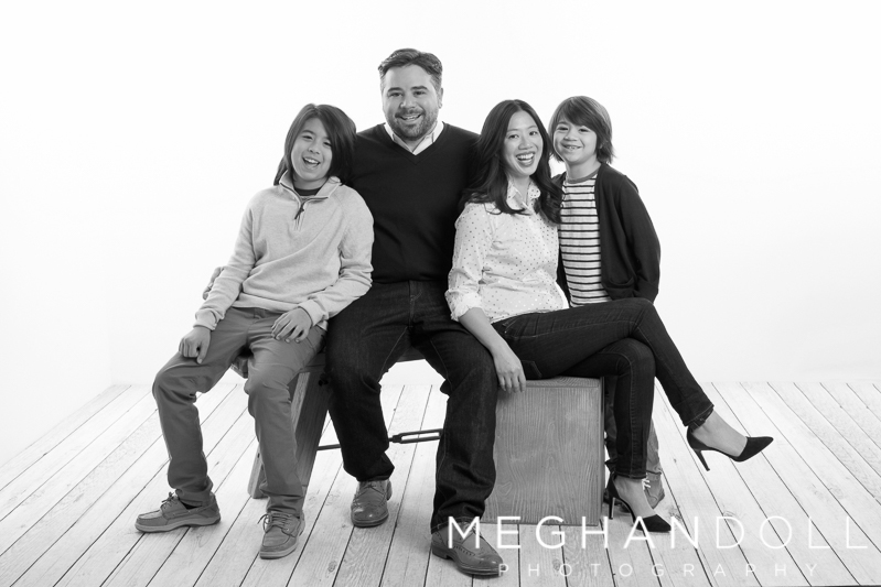 family-of-four-sits-and-laughs-together-in-black-and-white