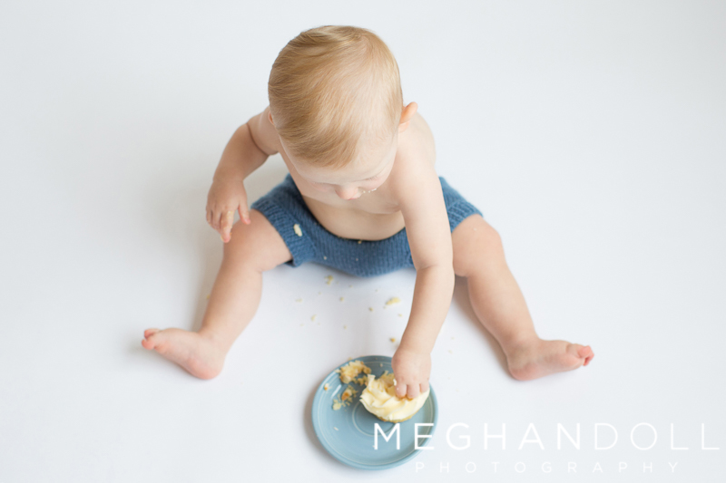 one-year-old-boy-in-blue-eating-cupcake
