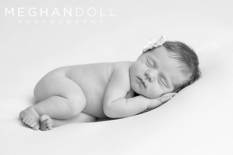 little-newborn-girl-sleeping-on-white