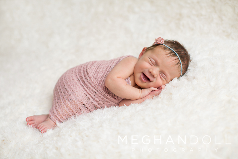 newborn-girl-in-pink-smiles-on-lace-blanket