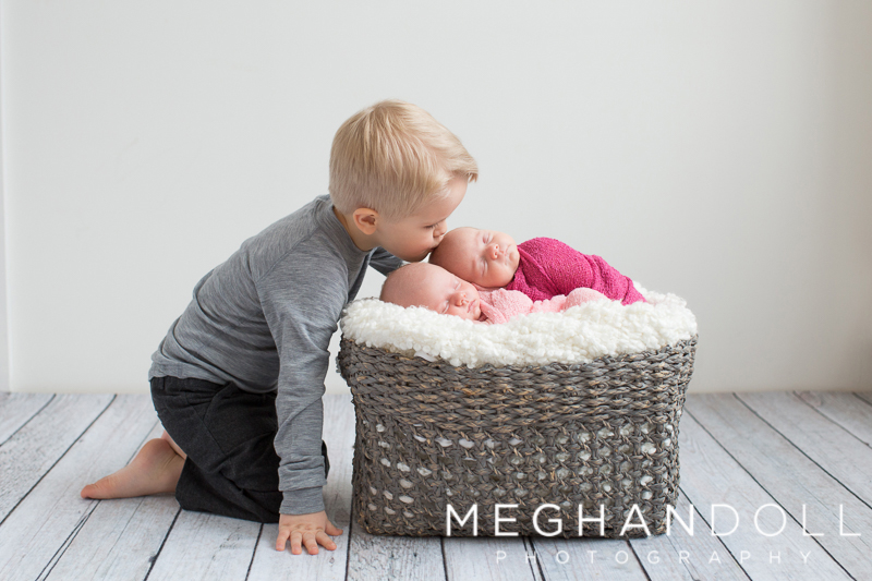 big-brother-kisses-newborn-twin-sisters-in-basket