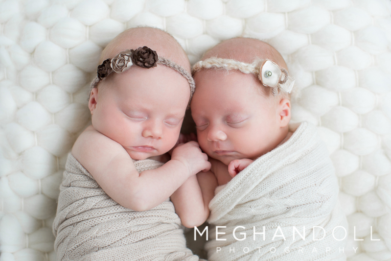 sweet-newborn-sisters-hold-hands