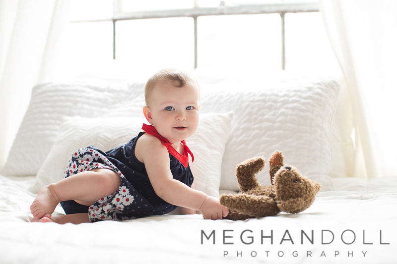 baby-girl-plays-with-teddy-on-bed