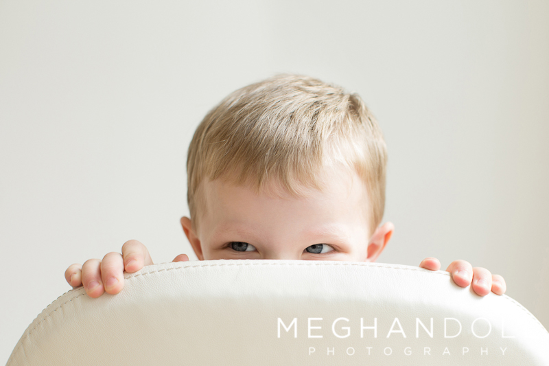 silly-boy-plays-peekaboo-on-white-chair