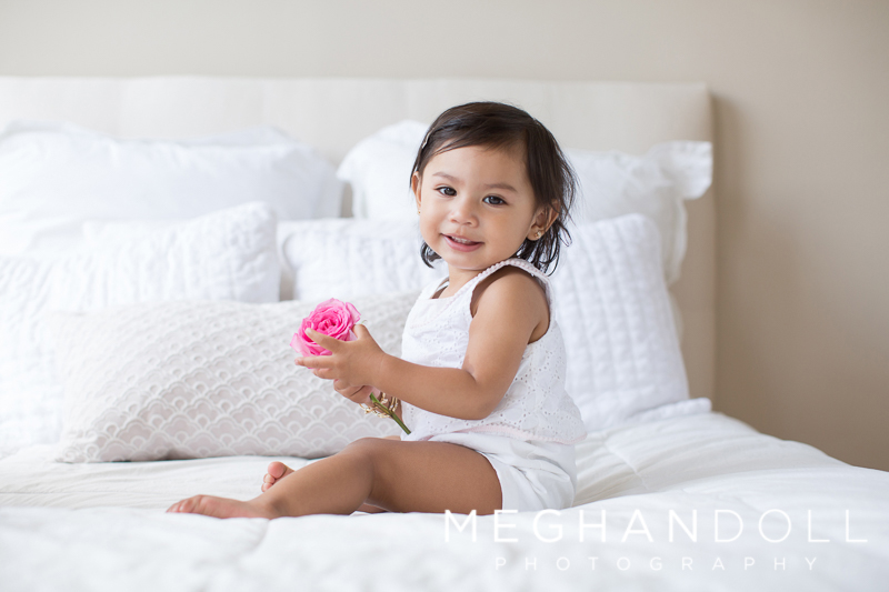 toddler-girl-plays-with-rose-on-white-bed