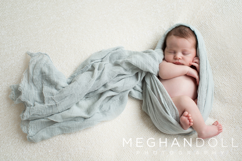 chubby-newborn-boy-sleeps-wrapped-in-light-blue