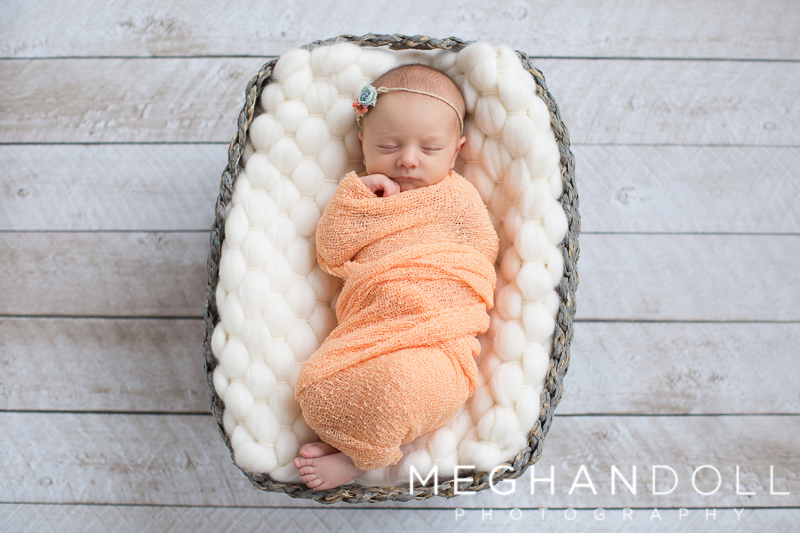 newborn-girl-in-orange-sleeps-in-gray-basket