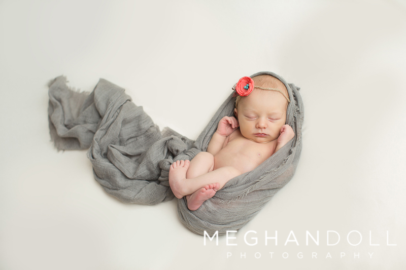 newborn-girl-wrapped-in-gray-sleeps-on-white-blanket