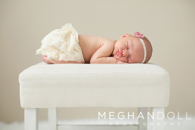 newborn-girl-sleeps-on-white-stool