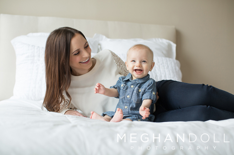 mom-laughs-with-six-month-old-son-on-white-bed