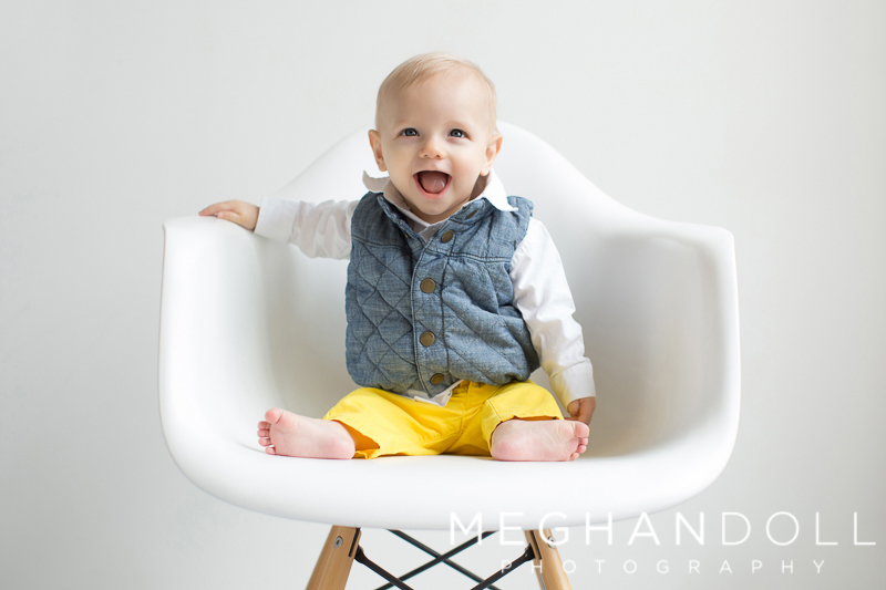 six-month-old-boy-in-yellow-pants-sits-on-white-chair