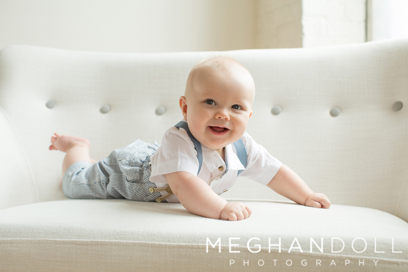 chubby-six-month-old-baby-lays-on-his-belly-on-white-button-couch