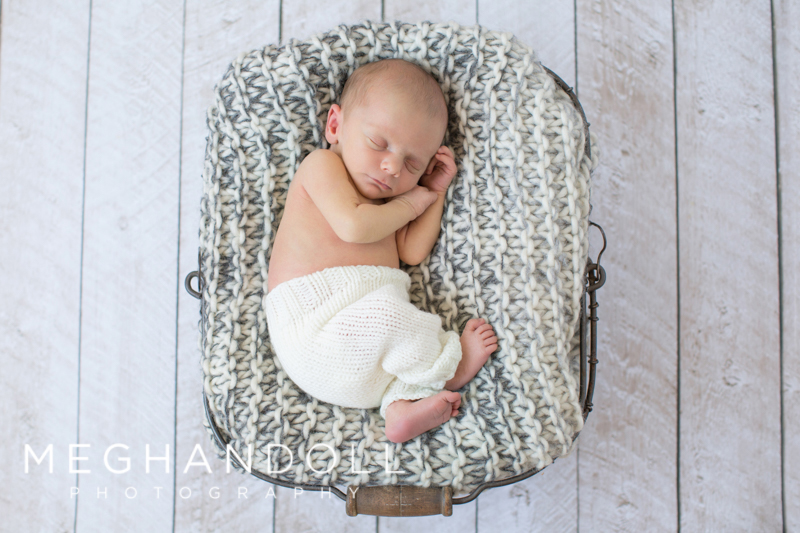 baby-boy-snuggled-in-metal-basket-with-crochet-blanket-2