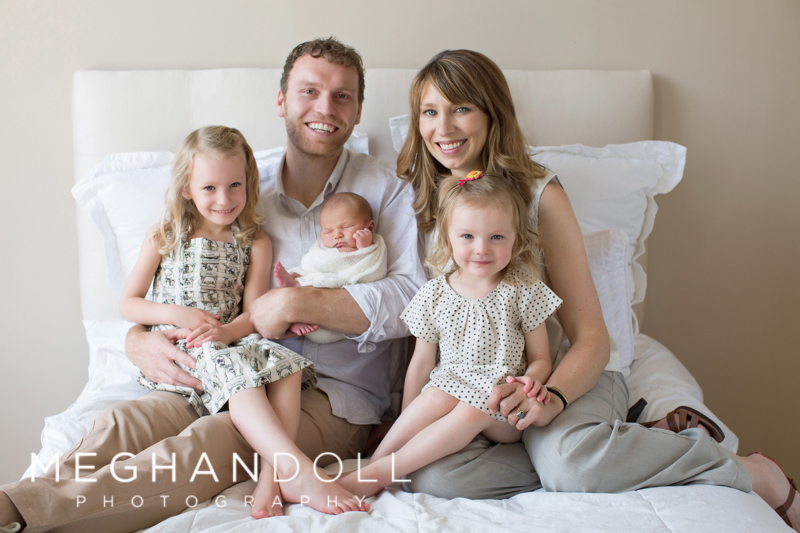 family-of-five-sitting-on-bed-with-newborn
