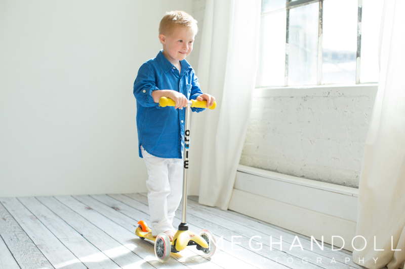 young-boy-in-studio-riding-scooter.jpg