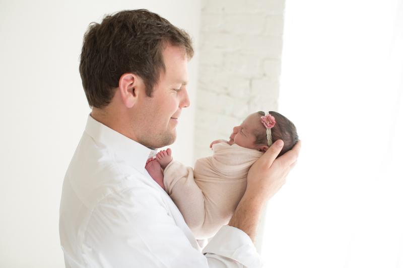 proud-dad-holding-newborn-daughter.jpg