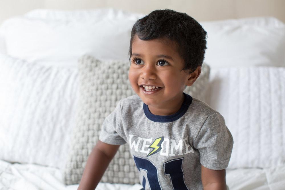 Little_boy_smiling_on_bed.jpg