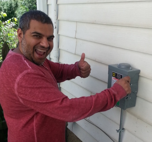 Yogesh pulls the lever to commission the solar panels on June 1, 2015.