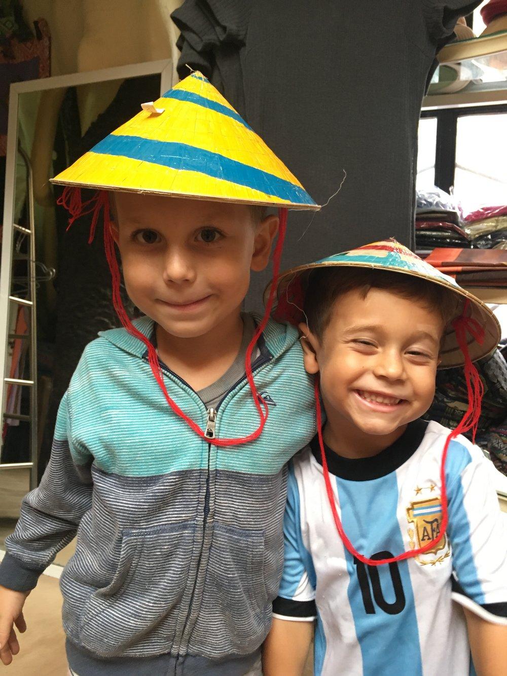 Probándose sombreros en una tienda en Vietnam. Ay cómo quería comprárselos, pero no podíamos cargarlos.