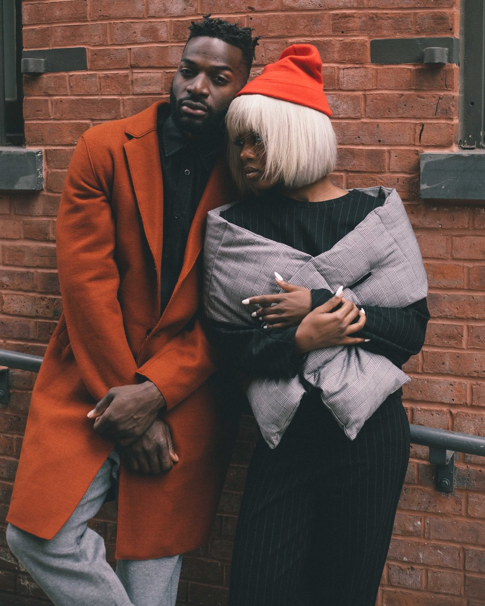 male model in orange jacket. female model in black pin suit. fashion photography captured by jarrod anderson in new york city