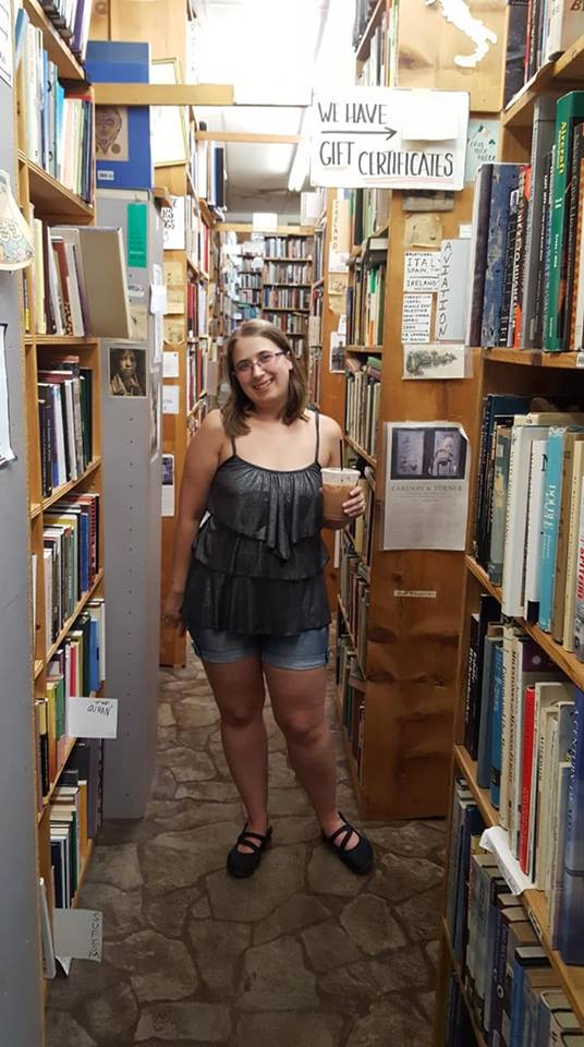 girl with a coffee surrounded by bookshelves