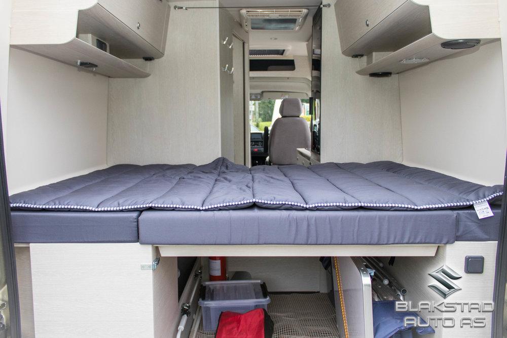 Soveplasser - Bobilen er registrert med 4 sitteplasser og 4 soveplasser. Det er en dobbeltseng bak i bilen som har en egen soveavdeling. I tillegg finnes det en dobbeltseng foran i bilen som med enkle grep settes sammen. Det spesielle med senga foran er at den er komplett for 2 voksne og man slipper å bruke fører- eller passasjersete for å bygge opp denne. Det viser seg at den ofte brukte løsningen i denne type bobil er egnet kun for barn. Vår løsning gir bedre komfort og mulighet til soveplaser for 4 voksne. Løsningen er patentert.
