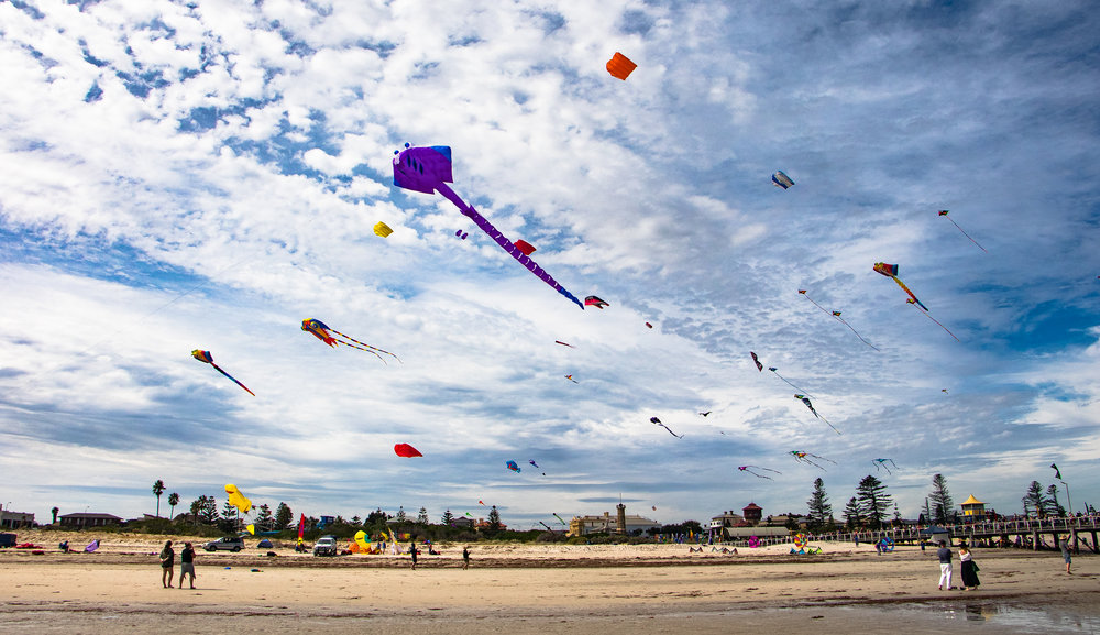 The Adelaide International Kite Festival hit the shores of Semaphore over the Easter weekend.  At the end of a cooler week for Adelaide, winds were expected to pick up for the colours and canvas. This forecast was incorrect, and while the smaller kites torn through the blue, the larger ones struggled to take to the air.  It was still a fantastic day for photos though. Lucid and trippy cloud patterns coloured the sky, and there was plenty of kinetic movement to play with.  The shoot was not entirely awesome. It was a bright day and, as a result, it was harder to coordinate the iris and white balance in such glare. Shoots like this are great examples of how useful a long range zoom lens with a decent aperture would be. Like shooting wildlife, I wished for more organic bokeh for these subjects. The end results for the day were some decent photos to look at, but I could have done better.  What do you guys think? Be sure to leave a down below and share your opinion.