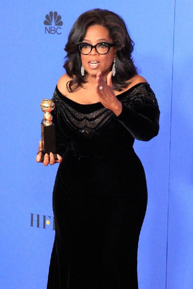 Oprah Winfrey: American talk show host, business woman, and philanthropist, posing with an award.