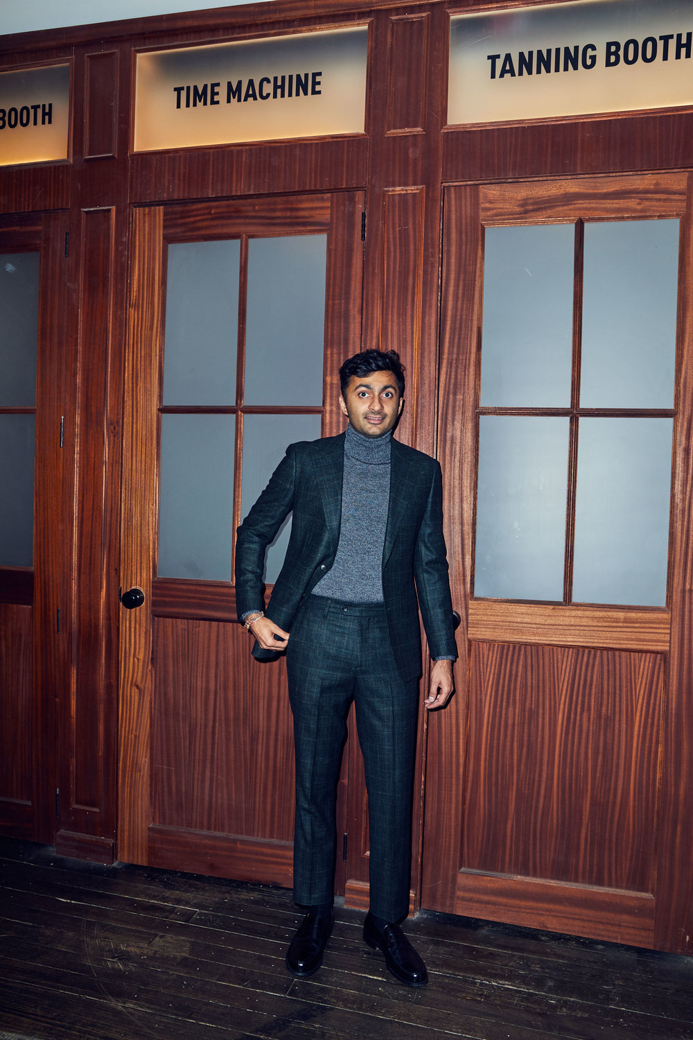 Moments later, in front of the fake time machine, Nimesh wears the    Premium Italian Wool Suit (Hayden Green Glenplaid)    and the    Merino Turtleneck Sweater (Grey Marl)