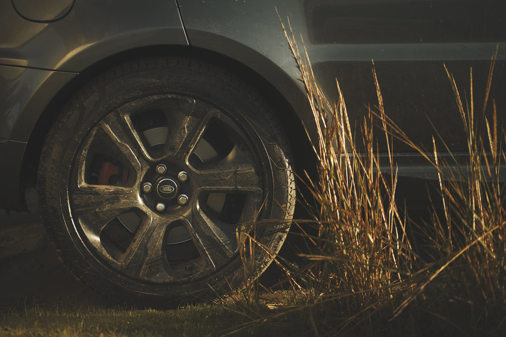 Close up of Range Rover sport alloy wheel on the beach, with tyre tracks and reeds in the golden sunlit. commercial advertising automotive photography. off road in the cumbria countryside