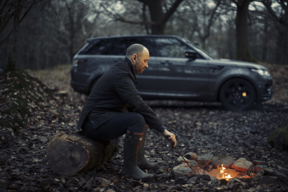 Chef Simon Rogan uses a bbq barbecue during Range Rover Sport Commercial advertising automotive photography shoot.  off road in the Lake District, Cumbria for Land Rover. Packshot. Highlighting the Great British Outdoors, craftmanship, rural life and heritage brands. food photography still life.