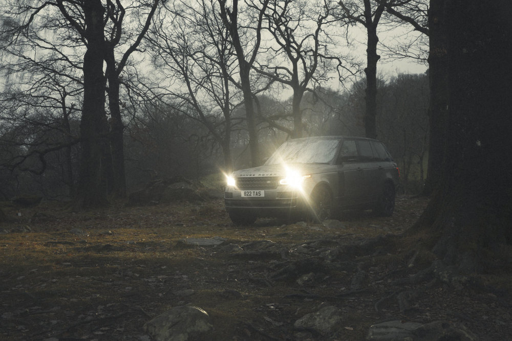 Range Rover in murky moody lighting at dawn, in wilderness during a Commercial advertising automotive photography shoot.  off road in the lake district for Land Rover. Packshot. Highlighting the Great British Outdoors, craftmanship, rural life and heritage brands. food photography still life.