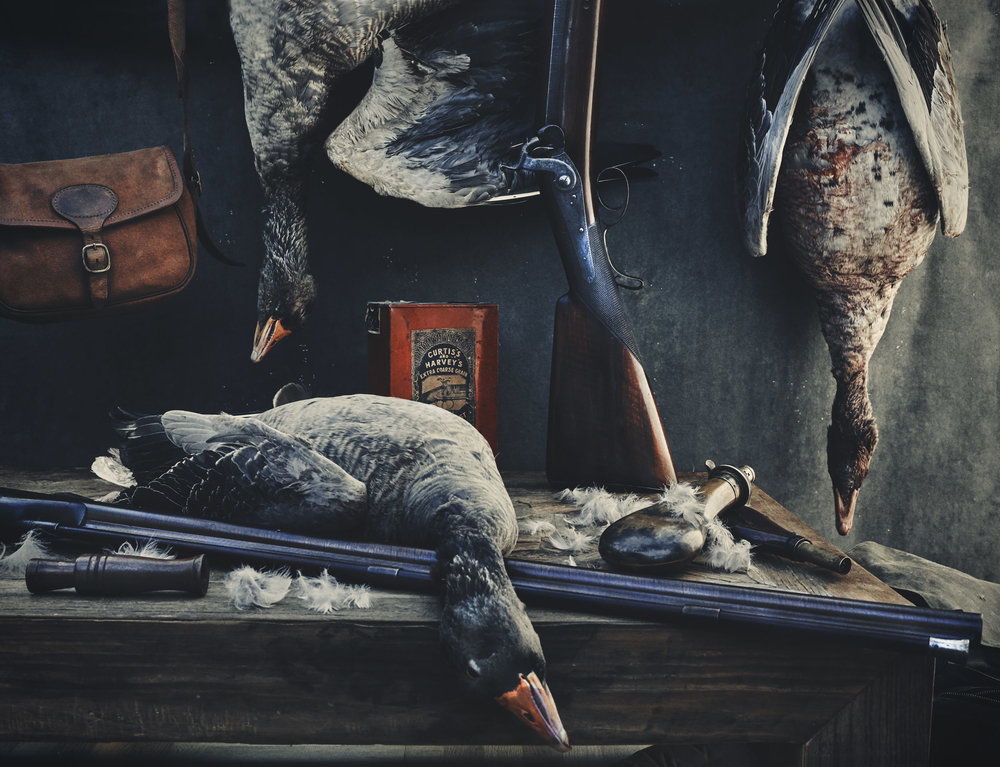 still life of wildfowl and shotgun photographed by Matthew Lloyd against a painted background in the style of the Dutch Masters