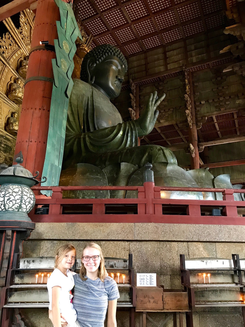 Autumn and Eden stand beside the Big Buddha. See Buddha's hand up there? Now picture a full-grown man standing in it, and that might help you see how large he is!