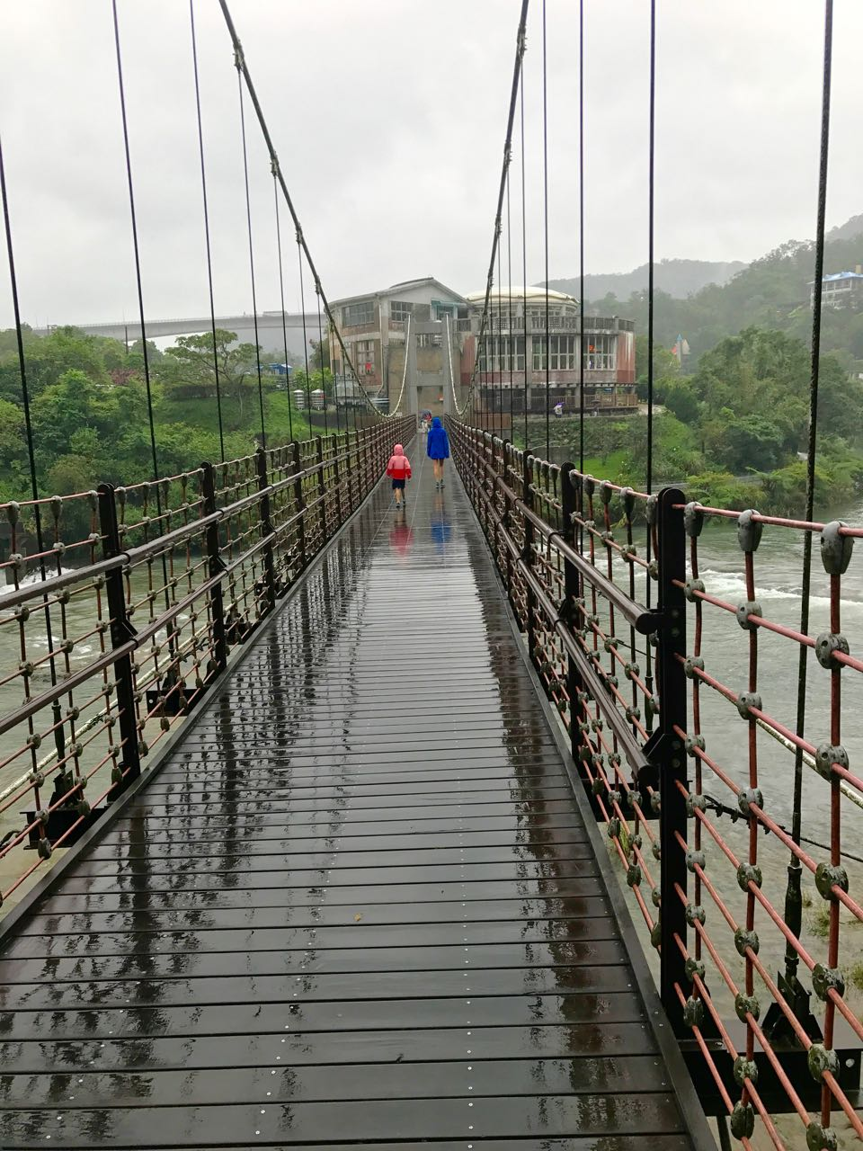Autumn and Eden cross the rope bridge suspended over the Keelung River.