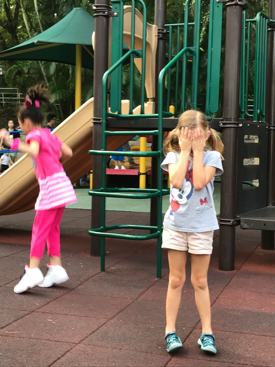 Eden plays hide and seek with a new friend at Kowloon Park in Hong Kong.