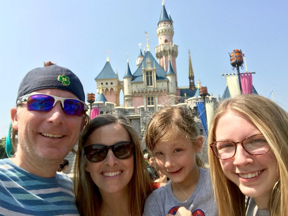 Smiling faces in front of Hong Kong Disneyland's Sleeping Beauty Castle.