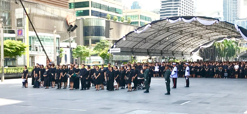 Thousands wait patiently outside of Center World (the tenth largest shopping complex in the world) to pay homage to King Bhumibol Abulyadej on cremation day.