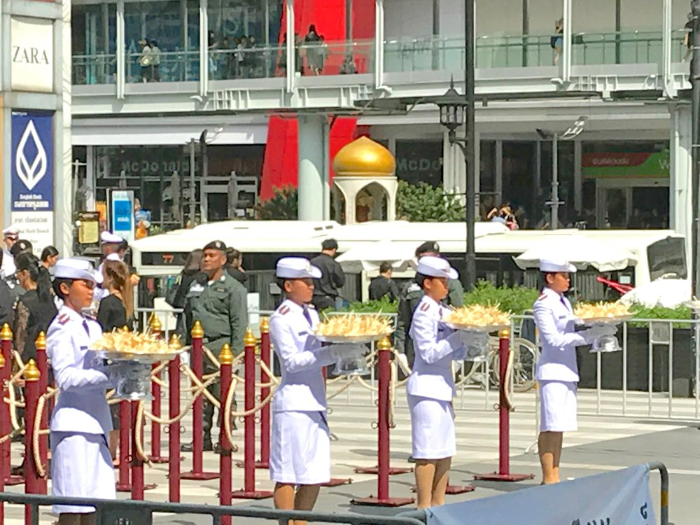 Uniformed men and women ensure a reverent and organized ceremony for thousands of mourning Thai people who loyally present sandalwood flowers (see the flowers on the large plates) on the day of the king's cremation.