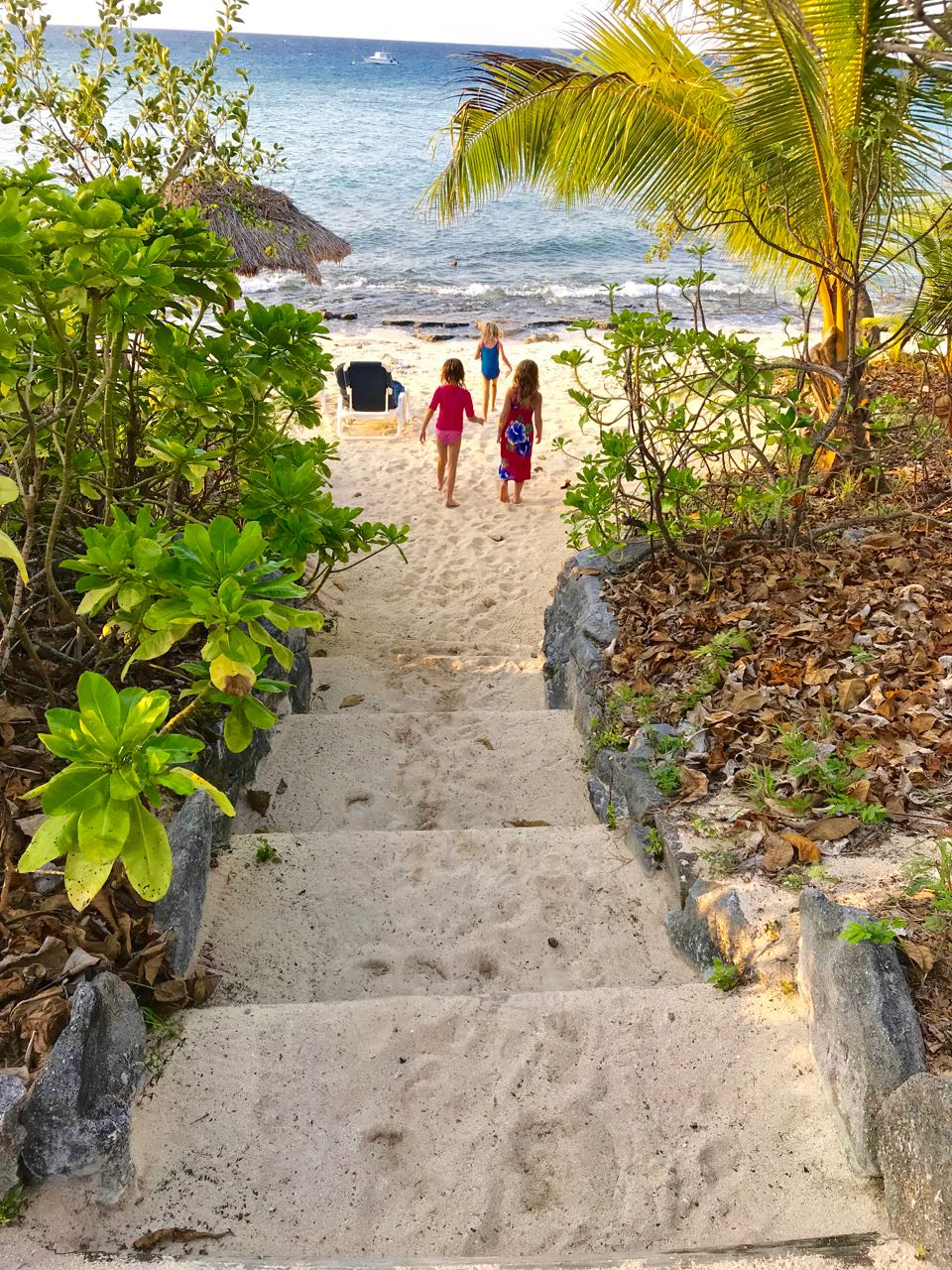 Eden and her new friends Rachel and Anabel walking down our bure's front steps to the beach