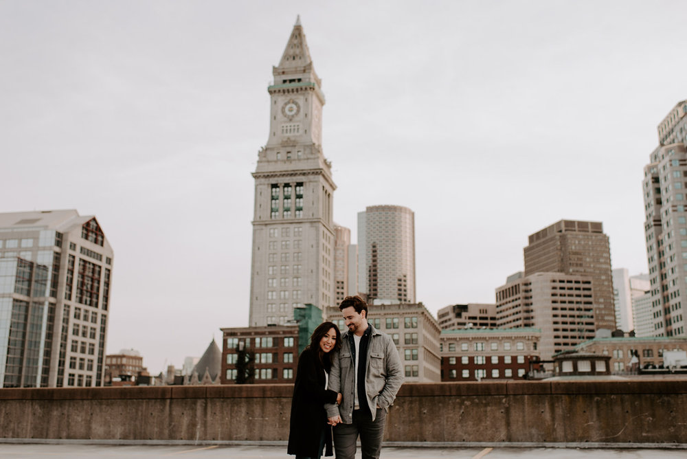 You guys, Grace and Kevin flew all the way from San Francisco!!! Kevin's family lives in New England, and since they're getting married on the west coast, they thought it would be great to incorporate Boston for their engagement photos and I could not agree more.  I got to show off all of my favorite Boston spots, starting off in Beacon Hill at one of my favorite pubs,  The 21st Amendment . It's a classic Boston spot, so cozy, lots of a dark wood, and great selection of beers. A lot of people jokingly ask me if they should have a drink or do a shot before their photos to loosen up, but the honest answer is yes! Let's also be a bit honest and say that no one looks good in drunk photos, but let's have a drink together to chat, catch up, and work your nerves out. I promise to take you to cool spots around town. We then explored my favorite neighborhood, Beacon Hill (I did spend three years living there). From there we jumped into a Lyft — which Grace and Kevin met in a Lyft, it was fate! — to  Faneuil Hall  and  Quincy Market  for a not so hidden photography gem, the roof of the Hard Rock Cafe parking garage. I'm not joking! It has a killer view of the state street buildings, clock tower, and a glimpse of the harbor buildings too. To round out our time together, we headed to the BU bridge which has an amazing skyline view of the Prudential Center and the Back Bay skyline. It can't be beat! And if it can, hit me up I need to know about it!  Grace and Kevin you guys are FUN, like really fun. Being with you, I could see that you care so deeply about each other, and are so excited to explore the world together for the rest of your lives. Thank you for allowing me to show you all around Boston and please switch coasts so we can do this all of the time!
